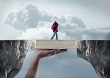 Scholarship surreal peaks. Young man passes from a peak to another on a book. The concept of scholarship stock photos