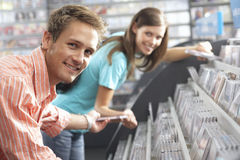 Young Man Passing CD To Woman In Record Shop, Bending Down, Smiling, Side View, Portrait Stock Image