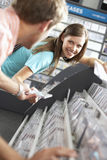 Young man passing CD to woman in record shop, bending down, smiling, side view, focus on background (tilt) Stock Photos