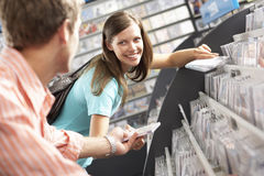 Young man passing CD to woman in record shop, bending down, smiling, side view, focus on background (tilt) Stock Photography