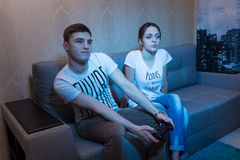 Young man passionate about a game sitting at home with his girlf Royalty Free Stock Photos