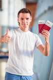 Young man with passports and boarding passes in airport Royalty Free Stock Photos