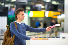 Young man with passports and boarding passes at Stock Photo