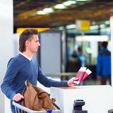 Young man with passports and boarding passes at Royalty Free Stock Photo