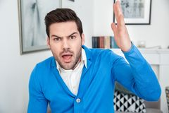 Young man patient waiting psychology session aggresive. Young male client waiting psychology therapy raising hand up aggresive angry about situation looking Stock Photos