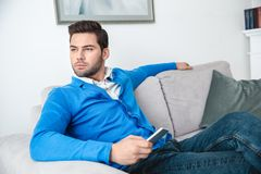 Young man patient waiting psychology session looking out the window. Young male client waiting psychology therapy sitting on sofa holding smartphone looking out Stock Photo