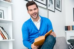 Young man patient waiting psychology session reading book cheerful. Young male client waiting psychology therapy reading book story looking camera smiling royalty free stock photography