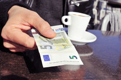 Young man paying the bill in the terrace of a cafe. Closeup of a young man with a cup of coffee paying the bill in the terrace of a cafe with a five euros Stock Photography