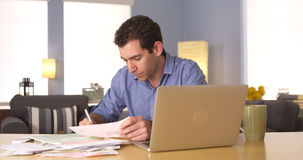 Young man paying bills at home Stock Image