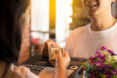 Young man paying cash at cafe and restaurant. Customer and woman cashier holding money with smiling face, bokeh blurred background Royalty Free Stock Photography