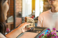 Young man paying cash at register counter . Customer and woman cashier holding money with smiling face, bokeh blurred background,business concept Royalty Free Stock Photo