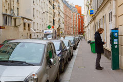 Young man paying at parking meter in Paris Stock Image
