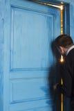Young man peeking in the door slot. Stock Photography