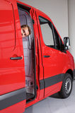 Young man peeking through van door Stock Images