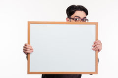 Young man peeping from blank board Royalty Free Stock Image