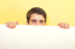 Young man peeping or looking over a white board. Portrait of an attractive young man peeping or looking over a white board against uniform background Stock Photography
