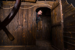 Young Man Peering Out From Cabin of Wooden Ship Stock Photos