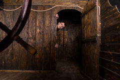Young Man Peering Out Doorway of Wooden Ship Royalty Free Stock Images