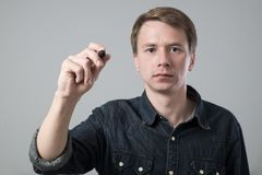 Young man with pen. Writing on virtual screen isolated on grey stock photos