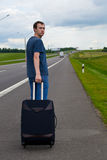 The young man pending on road with suitcase Stock Image