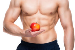 Young man with perfect body holding red apple. Stock Images