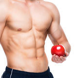 Young man with perfect body holding red apple. Royalty Free Stock Photos