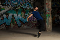 Young man performing a dance routine. Profile view of a good looking young male dancer performing a dance routine in front of a graffiti wall Royalty Free Stock Images