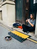 A young man performing with flute instrument on the street, Young man performer Stock Photo