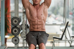 Young Man Performing Hanging Leg Raises Abs Exercise Royalty Free Stock Photography