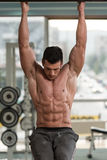 Young Man Performing Hanging Leg Raises Abs Exercise Royalty Free Stock Images