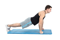 Young man performing push-ups exercise on fists. On white background royalty free stock image