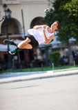 Young man performing somersault in the street. Young athlete performing sports acrobatics in city street, he doing somersault. Shot in motion Stock Photos