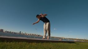 Young man performs acrobatic flip on the edge of a cliff overlooking the river and cityscape. Slow motion stock video