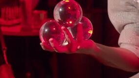 A young man performs amazing contact juggling with transparent balls in red lighting. A party. Close up.