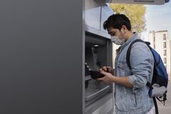The young man performs his transactions from the bank atm using his protective mask