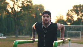 Young man performs a power Exercise On Uneven Bars. Young bearded man practicing on uneven bars in the park at dawn stock video