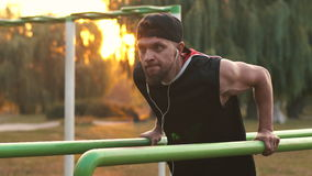 Young man performs a power Exercise On Uneven Bars. Young bearded man practicing on uneven bars in the park at dawn stock video footage