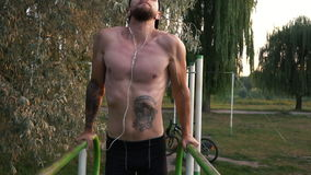 Young man performs a power exercise on uneven bars. Young bearded man practicing on uneven bars in the park at dawn, slow motion stock video