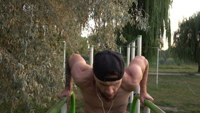 Young man performs a power exercise on uneven bars. Young bearded man practicing on uneven bars in the park at dawn, slow motion stock footage