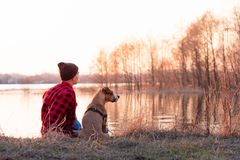 Young man and pet dog sit by lake at sunset in spring or autumn. stock image