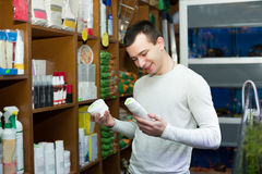 Young man with pet supplements in petshop Royalty Free Stock Photography