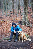 Young man petting dog. On winter forest Stock Photos