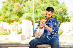 Young man petting his dog at the park. Good looking young man with a beard hugging and petting his dog while they relax together at the park Royalty Free Stock Images