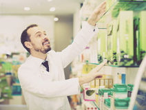 Young man pharmacist offering right drug. In drugstore Stock Photography