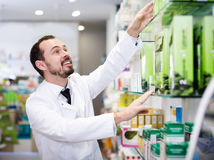 Young man pharmacist offering right drug. In drugstore Stock Image