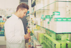 Young man pharmacist standing among shelves. Young man pharmacist wearing white coat standing among shelves in drug store Royalty Free Stock Photography