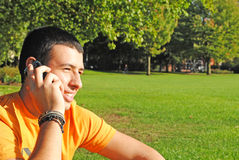 Young man on the phone. A young man talking on the phone while relaxing at the park Stock Photos