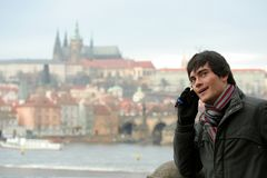 Young Man Phone. A young man with a cell phone, talking; the Prague Castle and the Vltava River in the background Royalty Free Stock Image