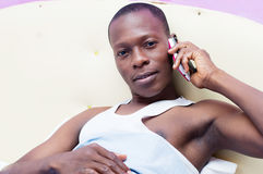 Young man on the phone in bed Royalty Free Stock Photo