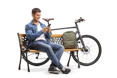 Young man with a phone and a bicycle sitting on a wooden bench. Isolated on white background Stock Photo